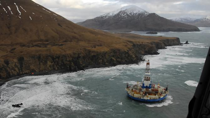 FILE - In this Jan. 3, 2013 file photo provided by the U.S. Coast Guard, two life rafts sit on the beach adjacent as the conical drilling unit Kulluk sits grounded 40 miles southwest of Kodiak City, Alaska. The united command overseeing the salvage of Royal Dutch Shell PLC drill barge that ran aground on a remote Alaska island will release minimal information on the vessel until an assessment is completed, a spokeswoman said. Shell's drill vessel Kulluk, a round barge with a derrick in its center, ran aground New Year's Eve on the southeast side of Sitkalidak Island near Kodiak Island.(AP Photo/U.S. Coast Guard, Petty Officer 2nd Class Zachary Painter, File)