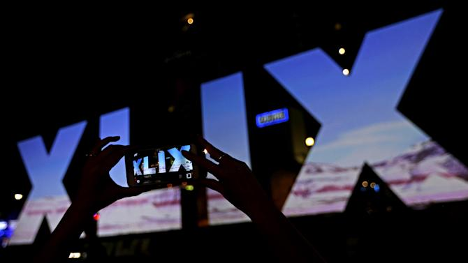 A woman takes a photo of Roman numerals for Super Bowl XLIX Wednesday, Jan. 28, 2015, in downtown Phoenix. The New England Patriots face the Seattle Seahawks in Super Bowl XLIX on Sunday in Glendale, Ariz