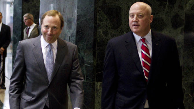 """FILE - This Aug. 14, 2012, file photo shows NHL commissioner Gary Bettman, left, and Bill Daly, deputy commissioner and chief legal officer, following collective bargaining talks in Toronto. The NHL is set to get back to the bargaining table Sunday, Dec. 30, 2012, with the locked-out players' association after a new contract offer from the league broke the ice between the fighting sides. """"We delivered to the union a new, comprehensive proposal for a successor CBA,"""" NHL deputy commissioner Bill Daly said in a statement Friday, Dec. 28. """"We are not prepared to discuss the details of our proposal at this time."""" (AP Photo/The Canadian Press, Chris Young, File)"""