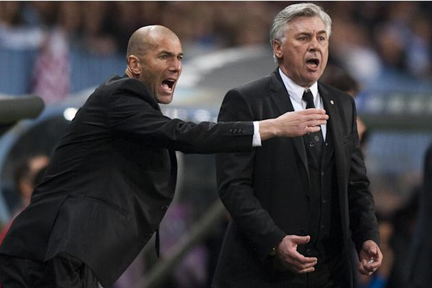 Real Madrid's assistant coach Zinedine Zidane from France, left, and coach Carlo Ancelotti from Italy, right, gesture during a Spanish La Liga soccer match at La Rosaleda stadium in Malaga, Spain,