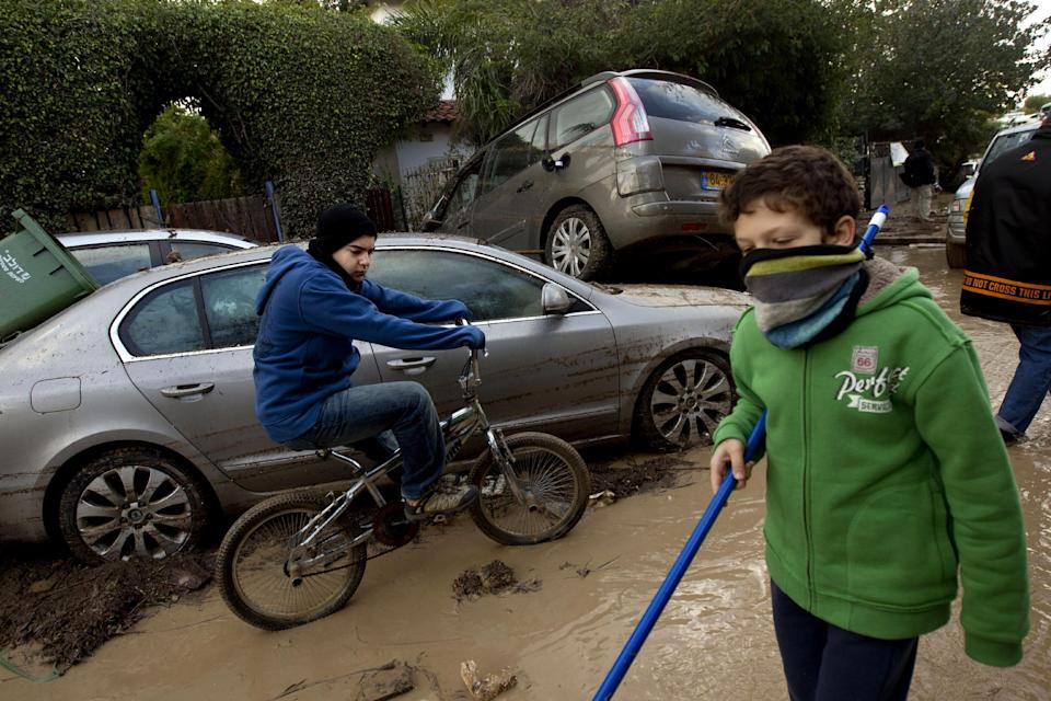 Residences clean mud next to a pile of cars after a flood by torrential rains that hit the village of Bat Hefer, central Israel, Wednesday, Jan. 9, 2013. About 200 homes were flooded and tens of cars were damaged by the flood. (AP Photo/Ariel Schalit)