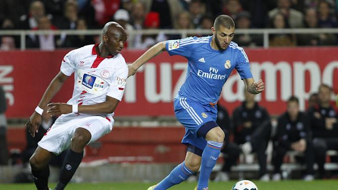 Real Madrid's Karim Benzema from France, right, and Sevilla's Stephane M'Bia from Camerum, left, vie for the ball  during their La Liga soccer match at the Ramon Sanchez Pizjuan stadium, in Seville, Spain on Wednesday, March 26, 2014