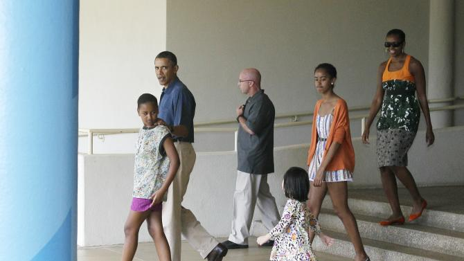 President Barack Obama and the first family leave the East-West Center after visiting an exhibit about the President's mother's anthropological work in Honolulu, Hawaii Sunday, Jan. 1, 2012. (AP Photo/Eric Risberg)