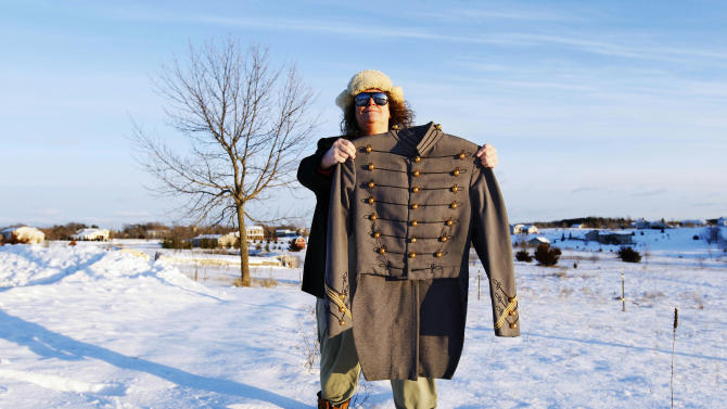 In this Dec. 20, 2012 photo, Mary Helen Taft displays a military jacket outside her home in Zimmerman, Minn. She bought the jacket at a consignment shop about 20 years ago, and the story of a similar jacket found in the debris of Superstorm Sandy prompted her to learn more about this jacket's past. With the help of the U.S. Military Academy at West Point, Taft has learned that the 80-year-old tunic was once worn by 1971 West Point graduate Joseph Francis Albano. (AP Photo/Genevieve Ross)