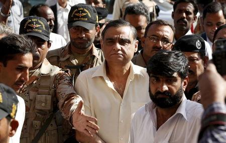 Police and Rangers soldiers escort Asim Hussain into Sindh High Court in Karachi, Pakistan