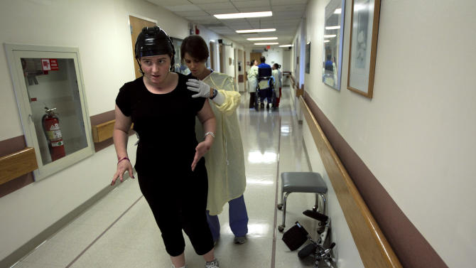 In this Wednesday, July 11, 2012 photo, Meg Theriault, of Salisbury, Mass., foreground, works with physical therapist Heather Meunier to practice walking at the Spaulding Rehabilitation Hospital in Boston. Meg is receiving physical therapy as part of her rehabilitation from a near-fatal traumatic brain injury suffered in a multi-fatal minivan crash in New Zealand on May 12, 2012. (AP Photo/Steven Senne)
