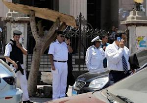 Members of special police forces stand guard as police investigate the car from which an explosive device attached to it detonated outside a court in the Heliopolis area in Cairo