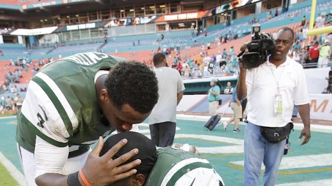 New York Jets quarterback Geno Smith (7) kisses the top of Demario Davis' (56) head at the end of an NFL football game against the Miami Dolphins, Sunday, Dec. 28, 2014, in Miami Gardens, Fla. The Jets defeated the Dolphins 37-24. (AP Photo/Wilfredo Lee)