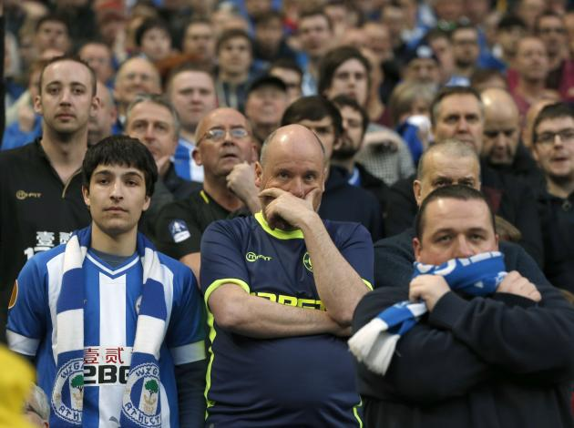 Wigan Athletic fans watch anxiously during their English FA Cup quarter final soccer match against Manchester City at the Etihad stadium in Manchester