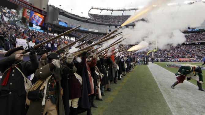A rifleman ducks under the fire during the pre-game entertainment before the AFC Championship NFL football game between the Baltimore Ravens and New England Patriots Sunday, Jan. 22, 2012, in Foxborough, Mass.  (AP Photo/Matt Slocum)