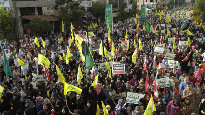 """Hezbollah supporters wave their flag and hold up Arabic banners that read, """"At your service God's prophet, America equals terrorism, and America does not equal freedom,"""" during a rally denouncing an anti-Islam film that has provoked a week of unrest in Muslim countries worldwide, in the southern suburb of Beirut, Lebanon, Monday Sept. 17, 2012. Hezbollah's leader Hassan Nasrallah, nor shown, who does not usually appear in public for fear of assassination, called for Monday's protests in Beirut, saying the U.S. must be held accountable for the film because it was produced in America. (AP Photo/Hussein Malla)"""