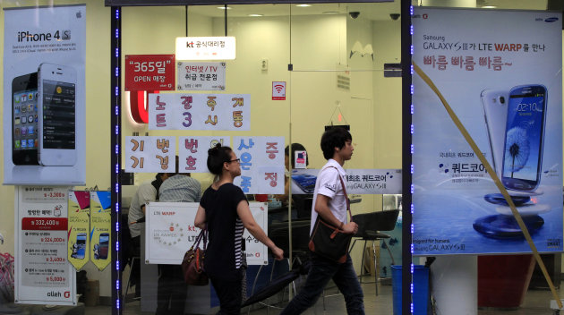 People walk past by banners advertising Samsung and Apple's smart phones at a mobile phone shop in Seoul, South Korea, Tuesday, Aug. 28, 2012. A U.S. jury's $1 billion verdict against Samsung for what rival Apple claimed was the illegal copying of its iPhone and iPad designs signals a turning point for the South Korean electronics giant known for its prowess in adapting the innovations of others and nimbly executing production. (AP Photo/Lee Jin-man)