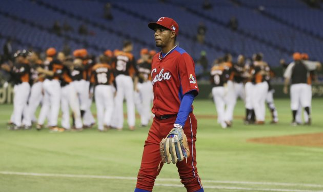 Cuba's shortstop Gonzalez walks off the field as Netherlands' players celebrate after defeating Cuba at the WBC second round game in Tokyo