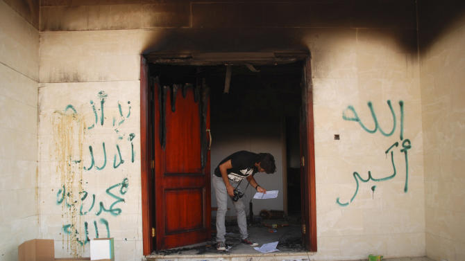 """FILE - In this Wednesday, Sept. 12, 2012 file photo, a man looks at documents at the U.S. consulate in Benghazi, Libya, after an attack that killed four Americans, including Ambassador Chris Stevens. The graffiti reads, """"no God but God,""""  """" God is great,"""" and """"Muhammad is the Prophet."""" Witness accounts gathered by The Associated Press give a from-the-ground perspective for the sharply partisan debate in the U.S. over the deadly incident. They corroborate the conclusion largely reached by American officials that it was a planned militant assault. But they also suggest the militants may have used a film controversy as a cover for the attack. (AP Photo/Ibrahim Alaguri)"""