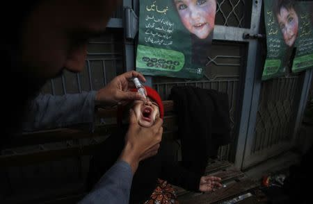 A girl receives polio vaccine drops at a government children's hospital in Peshawar
