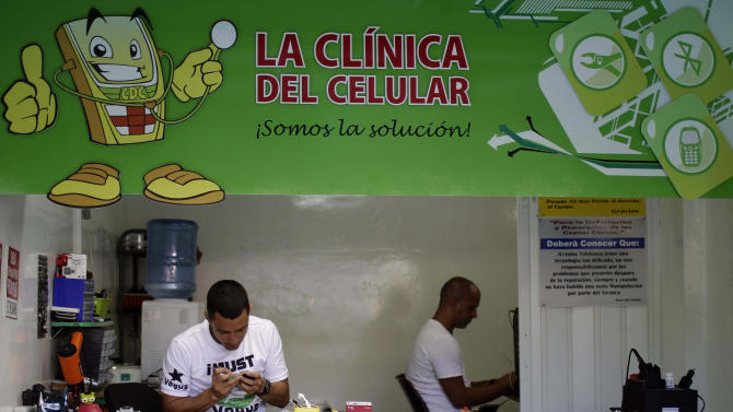 In this June 13, 2012 photo, Javier E. Matos, left, repairs a phone at The Cell Phone Clinic, a private business in Havana. For decades, Communist-run Cuba has essentially been free of commercial advertising. But it's a knotty problem for thousands of budding entrepreneurs who have embraced President Raul Castro's push for limited free-market reform. So they're turning to guerrilla marketing. (AP Photo/Franklin Reyes)