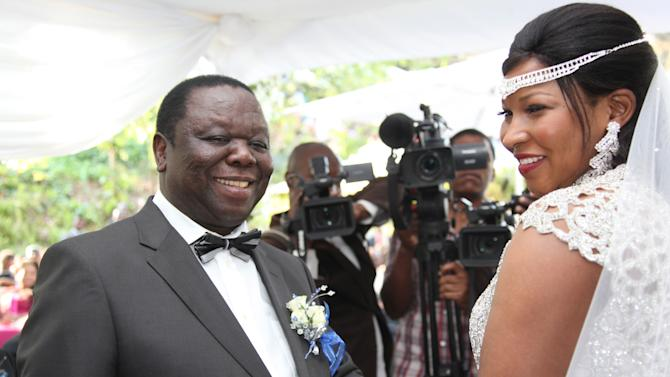 Zimbabwean Prime Minister Morgan Tsvangirai, left, is seen with his wife Elizabeth Macheka during a traditional wedding ceremony in Harare, Saturday, Sept. 15, 2012, despite a court ruling that canceled his marriage license on allegations that he would be committing bigamy. Tsvangirai, 60, and his bride exchanged vows and rings at a luxury convention facility in Harare but did not sign the legal marriage register. A court on Friday declared Tsvangirai already married under tribal law after seeing video footage of traditional bride price being paid last November to the family of another Zimbabwean woman. Polygamy is recognized in tribal law but not in Zimbabwe's national laws.(AP Photo/Tsvangirayi Mukwazhi)