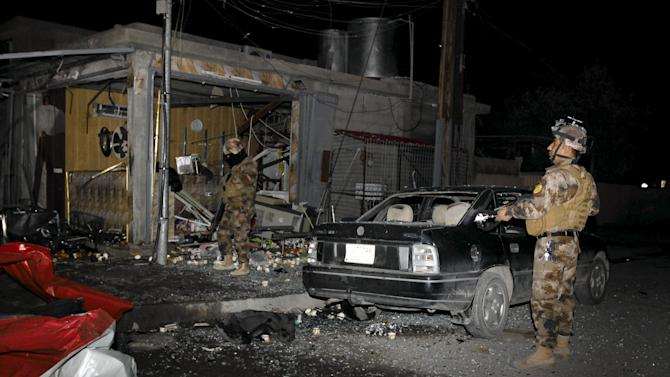 Members of the Kurdish security forces inspect the site of bomb attack in Kirkuk