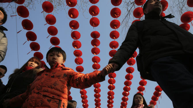 People walk under lanterns at the Longtan park as the Chinese Lunar New Year is celebrated in Beijing