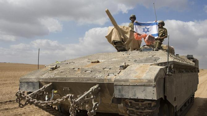 Israeli soldiers display their national flag from the top of an armoured personnel carrier as they deploy near Israel's border with the Gaza Strip on July 18, 2014
