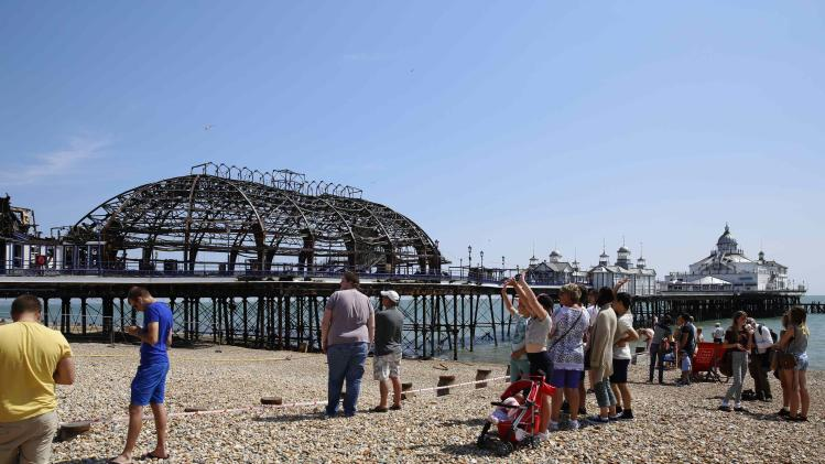 People walk on the beach to look at the burnt remains of a section of Eastbourne pier, in Eastbourne
