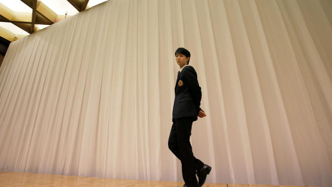 Japan's figure skater Yuzuru Hanyu waits for a photo session following a press conference ahead of the NHK Trophy figure skating in Osaka, western Japan, Thursday, Nov. 27, 2014. Even though he is not in top condition, Olympic and world champion Hanyu said his desire to qualify for the Grand Prix Final convinced him to take part in this weekend's NHK Trophy. (AP Photo/Shizuo Kambayashi)