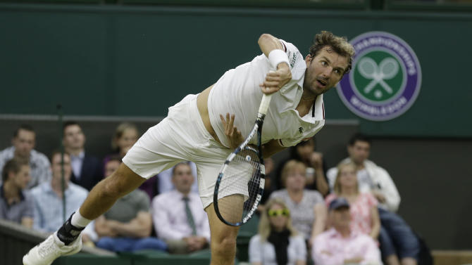 Julien Benneteau of France serves to Roger Federer of Switzerland during a third round men's singles match at the All England Lawn Tennis Championships at Wimbledon, England, Friday, June  29, 2012. (AP Photo/Alastair Grant)