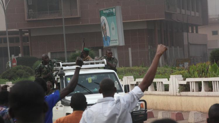 Civilians cheer as mutinous soldiers drive past in Bamako, Mali Wednesday March 21, 2012. Gunshots could still be heard in the Malian capital late Wednesday, hours after angry troops started a mutiny at a military base near the presidential palace. Soldiers stormed the offices of the state broadcaster, yanking both TV and radio off the air.(AP Photo/Harouna Traore)