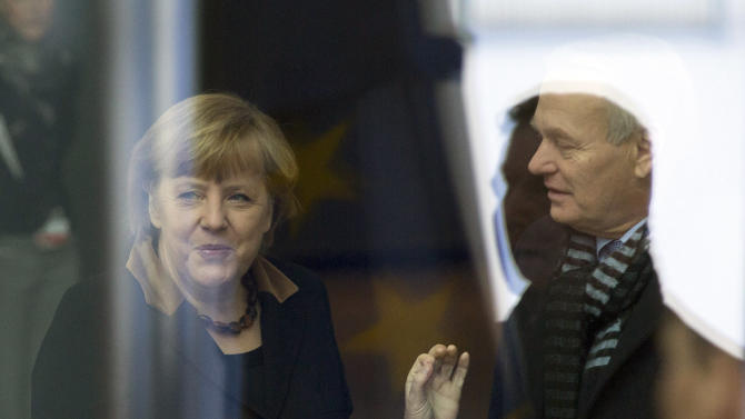 German Chancellor Angela Merkel, left, talks to French Prime Minister Jean-Marc Ayrault, right, at the Chancellery in Berlin, Germany, Tuesday, Jan. 22, 2013. France and Germany mark 50 years since they signed the Elysee Treaty, the post-war friendship pact between the former enemies. Pictures is taken through a window with reflections. (AP Photo/Gero Breloer)