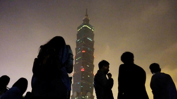 """Onlookers watch Taipei 101 building as it turns its lights off to observe international """"Earth Hour"""" campaign, Saturday, March 23, 2013, in Taipei, Taiwan. Around 100 people gathered outside the skyscraper Saturday, using energy saving LED lights to observe the global event that encourages people to turn off their lights for 60 minutes. (AP Photo/Wally Santana)"""
