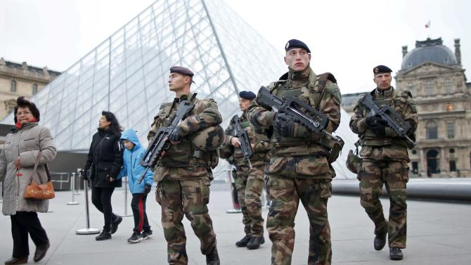 French soldiers patrol in front of the Louvre Museum Pyramid's main entrance in Paris, France