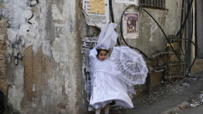 An ultra-Orthodox Jewish girl dressed as a bride stands on a sidewalk during celebrations marking Purim in Jerusalem