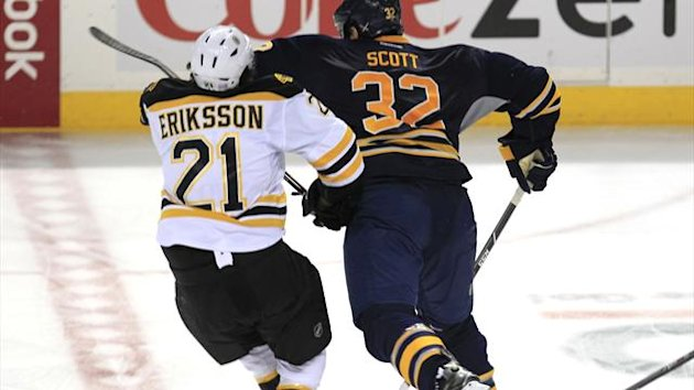 Buffalo Sabre, John Scott (32) checks Boston Bruin, Loui Eriksson (21) during third period action against at the First Niagara Center on Wednesday