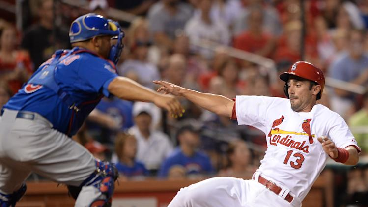 St. Louis Cardinals' Matt Carpenter (13) scores on a single by Matt Holliday as Chicago Cubs' Welington Castillo, left, waits for the ball in the first inning in a baseball game, Friday, Aug. 29, 2014, at Busch Stadium in St. Louis. (AP Photo/Bill Boyce)