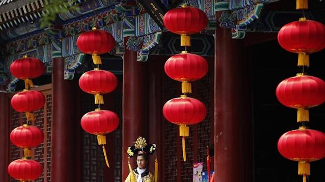 A restaurant promoter wearing a traditional Chinese costume waits for customers, in Beijing