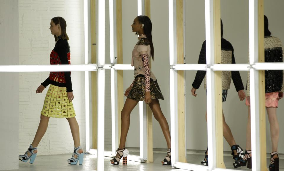Models walk through a grid of fluorescent lights at the conclusion of the presentation of the Rodarte Spring 2013 collection in New York, Tuesday, Sept. 11, 2012.  (AP Photo/Kathy Willens)