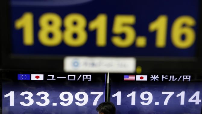 An employee of a foreign exchange trading company walks past monitors in Tokyo