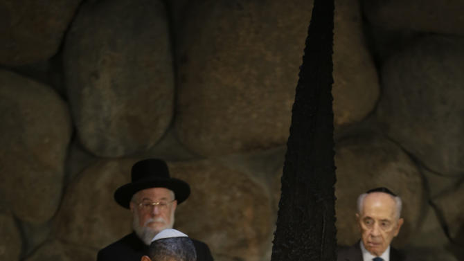 U.S. President Barack Obama, left, reignites the flame during his visit to the the Hall of Remembrance at the Vad Vashem Holocaust Memorial in Jerusalem, Israel, Friday, March 22, 2013. Standing behind Obama are Rabbi Israel Meir Lau, left, and Israeli President Shimon Peres. (AP Photo/Pablo Martinez Monsivais)