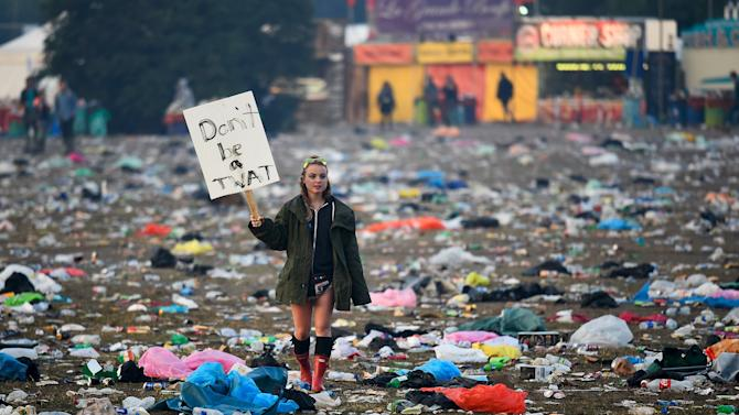 A reveller walks through rubbish left in front of the Pyramid Stage as they leave Worthy Farm in Somerset after the Glastonbury Festival