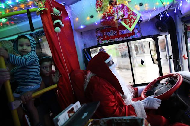 "Bus driver Edilson, also known as ""Fumassa"", drives while wearing a Santa Claus outfit inside an urban bus decorated with Christmas motives in Santo Andre"