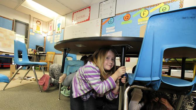 """Jaely John, 7, a student at Twin Lakes Elementary School in Federal Way, Wash.,  takes shelter under a table as she takes part in an earthquake drill, Thursday, Oct. 18, 2012. Millions of people took part in the """"Great Shakeout"""" earthquake drill across the country and elsewhere Thursday to practice and prepare for the possibility of real quakes in the future. (AP Photo/Ted S. Warren)"""