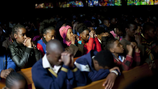 Worshipers pray in the Regina Mundi church in Soweto township on the outskirt of Johannesburg, South Africa, Sunday June 16, 2013. Former South African president Nelson Mandela remained hospitalized for the ninth day with an occurring lung infection. (AP Photo/Jerome Delay)