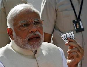 Hindu nationalist Modi holds a lotus cut-out after casting his vote at a polling station in Ahmedabad