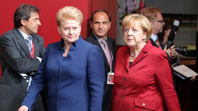German Chancellor Angela Merkel, right, walks with Lithuanian President Dalia Grybauskaite, second left, prior to a group photo at an EU summit on Thursday, Oct. 24, 2013. A two-day summit meeting of EU leaders is likely to be diverted from its official agenda, economic recovery and migration, after German Chancellor Angela Merkel complained to U.S. President Barack Obama that U.S. intelligence may have monitored her mobile phone. (AP Photo/Michel Euler)