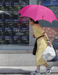 A woman walk by an electronic stock board at a securities firm in Tokyo,Thursday, Sept. 22, 2011. Japan's Nikkei 225 stock average ended the morning session down 142.84 points, or 1.63 percent, at 8,598.32. (AP Photo/Koji Sasahara)