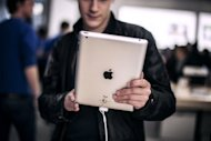 A customer test an iPad at a new Apple store in Lyon, France, on April 4. Apple said it had raked in a profit of $11.6 billion in the first three months of the year driven by record sales of iPhones and iPad tablet computers