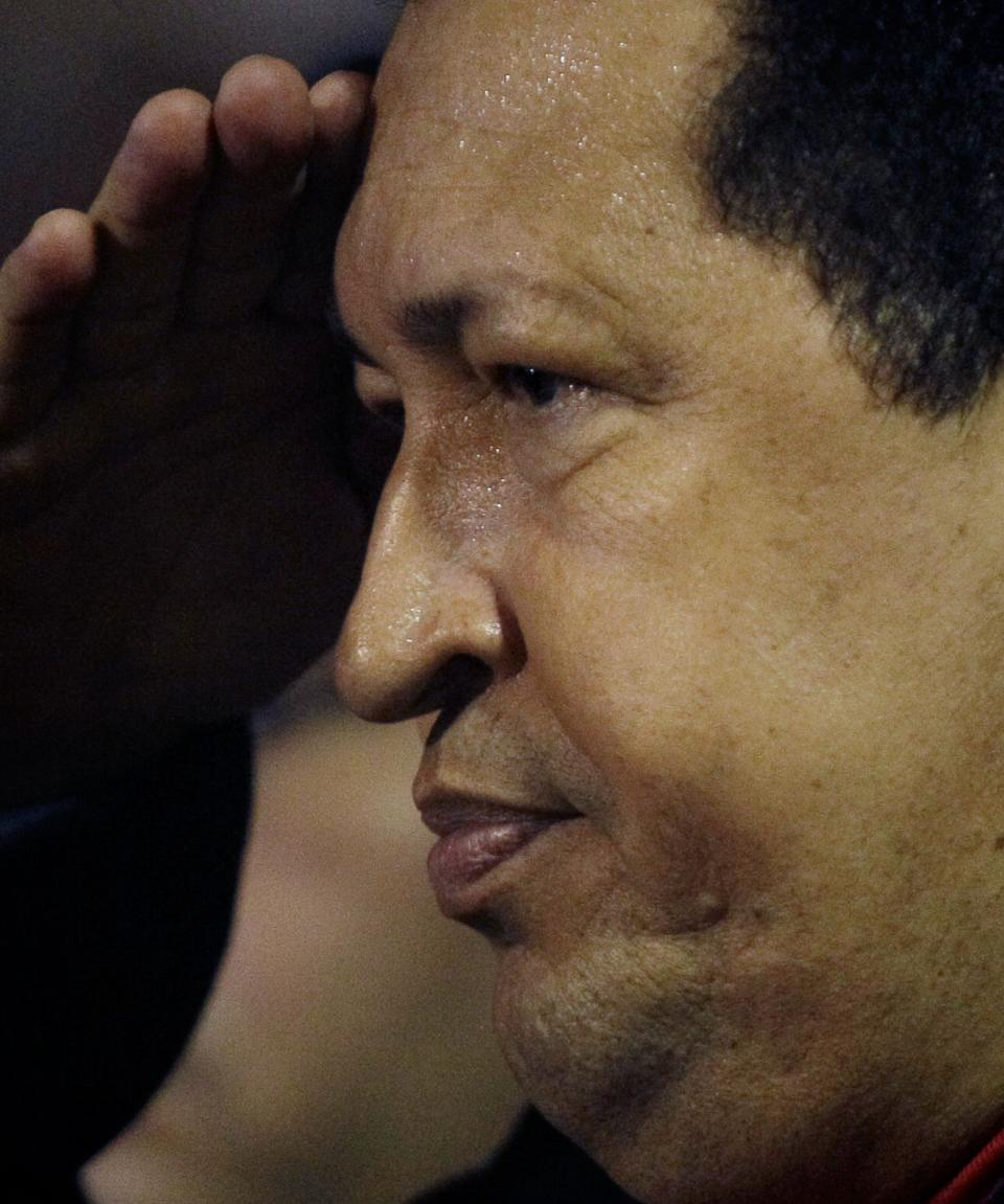 Venezuela's President Hugo Chavez salutes upon his arrival to the Simon Bolivar airport in Maiquetia , near Caracas, Venezuela, Friday, March 16, 2012. Chavez returned home Friday nearly three weeks after undergoing cancer surgery in Cuba. (AP Photo/Fernando Llano)