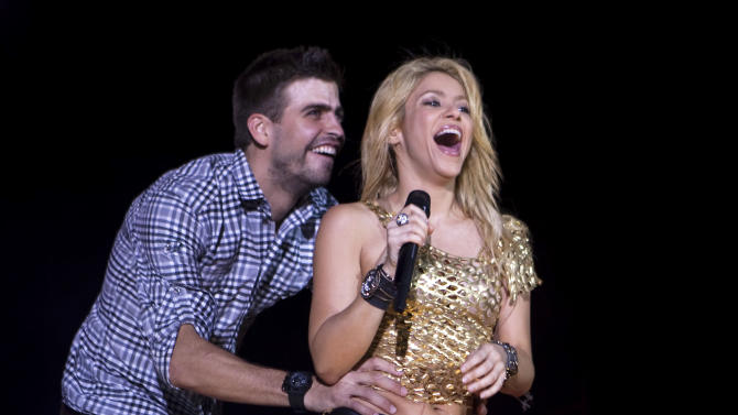 CORRECTS NAME TO SHAKIRA IN SECOND SENTENCE  - FILE - This May 29, 2011 file photo shows Colombia's singer Shakira performing with FC Barcelona soccer player Gerard Pique during The Sun Comes Out World Tour concert in Barcelona, Spain. It was announced on Wednesday, Jan. 23, 2013,  that singer Shakira Mebarak and soccer player Gerard Pique have welcomed a baby son, Milan Piqué Mebarak, born Tuesday, 22,  in Barcelona, Spain.  (AP Photo/Emilio Morenatti, File)