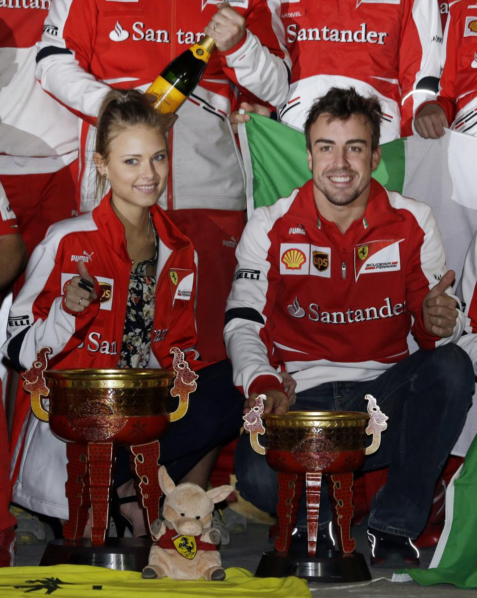 CORRECTS NAME OF WOMAN - Ferrari driver Fernando Alonso of Spain and Dasha Kaputina pose for a photo as the Ferrari team celebrate Alonso's win at the Chinese Formula One Grand Prix in Shanghai, China, Sunday, April 14, 2013. (AP Photo/Ng Han Guan)