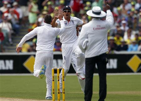 England's captain Cook celebrates with Swann after dismissing Australia's Rogers during the first day's play in the second Ashes test in Adelaide